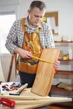 Mannen reparerar en stol i hans seminarium Fotografering för Bildbyråer
