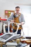 Mannen reparerar en stol i hans seminarium Royaltyfria Bilder
