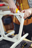 Mannen reparerar en stol i hans seminarium Arkivbild