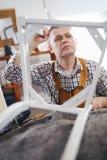 Mannen reparerar en stol i hans seminarium Royaltyfri Fotografi