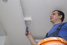 Mannen reparerar huset inom med rullen och hinken Royaltyfri Bild