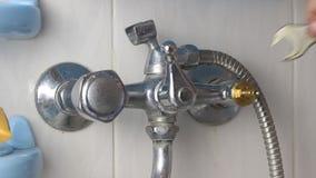 Mannen reparerar vattenkranen i badrummet, ändrar axeln, närbild stock video