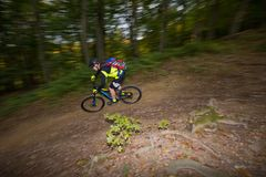 Mannen rider e-cykeln som är sluttande på skogslinga arkivbild