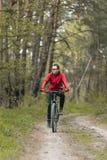 Mannen rider en cykel i skogen Royaltyfria Foton