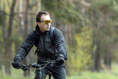 Mannen rider en cykel i skogen Fotografering för Bildbyråer