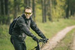 Mannen rider en cykel i skogen Royaltyfri Bild