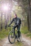 Mannen rider en cykel i skogen Arkivbilder