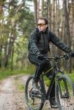 Mannen rider en cykel i skogen Arkivfoto