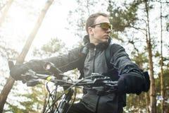 Mannen rider en cykel i skogen Arkivfoton