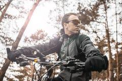 Mannen rider en cykel i skogen Arkivbild