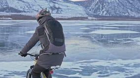 Mannen rider en cykel på is Cyklisten är iklädd en grå färg klår upp ner, ryggsäcken och hjälmen Is av det djupfryst royaltyfri fotografi