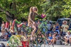 Mannen rider en dekorerad cykel ståtar in Royaltyfri Foto
