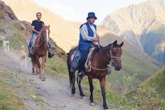 Mannen rider en h?st i bergen, Kaukasus, Georgia royaltyfri foto
