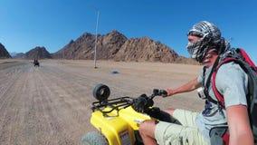 Mannen rider en kvadratcykel i öken av Egypten och skjuter sig på en handlingkamera lager videofilmer