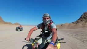 Mannen rider en kvadratcykel i öken av Egypten och skjuter sig på en handlingkamera stock video
