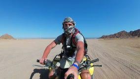 Mannen rider en kvadratcykel i öken av Egypten och skjuter sig på en handlingkamera arkivfilmer