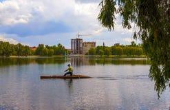 Mannen ror på ett kajakfartyg på den Ivano-Frankivsk stadssjön i sp Royaltyfri Fotografi