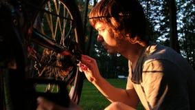 Mannen roterar ett hjul på en upturned cykel, grabben reparerar eker på solnedgången i parkerar fotografering för bildbyråer