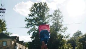 Mannen roterar runt om repet som rymmer hans händer bak honom Det 360 grad rotationstricket farligt jippo lager videofilmer
