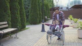 Mannen rullar en lycklig tonåring i en rullstol i parkera Royaltyfria Bilder