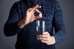 Mannen rymmer en minnestavla klar att upplösa pillret i vatten royaltyfri foto