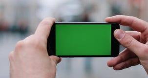 Mannen rymmer en smartphone med den gröna skärmen i hans armar som står på gatan lager videofilmer