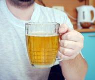 Mannen rymmer ett exponeringsglas av öl i hand Royaltyfria Bilder