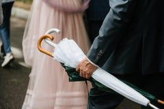 Mannen rymmer ett vitt stängt paraply från regnet royaltyfria bilder