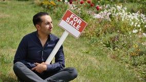 Mannen rymmer etttecken som annonserar en försäljning arkivbilder