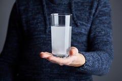 Mannen rymmer exponeringsglas av vatten med det upplösta pillret royaltyfri foto