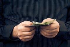 Mannen rymmer händer polerar pengar Arkivfoto