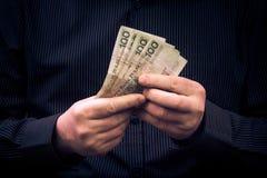 Mannen rymmer händer polerar pengar Royaltyfri Fotografi
