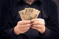Mannen rymmer händer polerar pengar Arkivbild