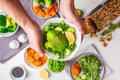 Mannen rymmer i hans händer en bunke av grön sallad från grönkål och avokadot Sund tabell för strikt vegetarianmatmatställe, bäst arkivfoton