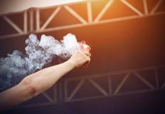 Mannen rymmer i hans hand r?ka och en brinnande r?d flammabrand royaltyfri fotografi