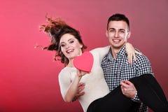 Mannen rymmer kvinnan med pappers- hjärta Arkivbild