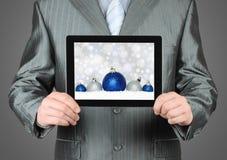 Mannen rymmer minnestavlaPC med julsammansättning Royaltyfri Foto