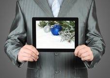 Mannen rymmer minnestavlaPC med julsammansättning Arkivbilder