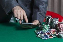 Mannen rymmer smartphonen, slå vad på online-kasinot royaltyfri foto