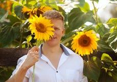 Mannen rymmer solrosen framme av framsidan royaltyfria foton