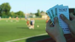 Mannen rymmer vinst från bookmakerkontoret, i händerna av europengarna i bakgrunden av stadion arkivfilmer
