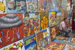 Mannen säljer arbeten av lokala konstnärer på gatan i Santo Domingo, Dominikanska republiken Fotografering för Bildbyråer