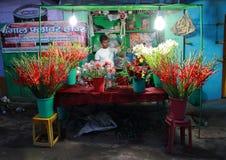 Mannen säljer blommor som är utomhus- i Varanasi, Indien Fotografering för Bildbyråer