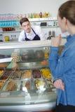 Mannen säljer glass i glasslager arkivfoto