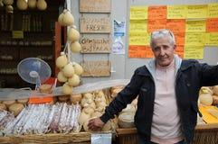 Mannen säljer ost och salami royaltyfri bild