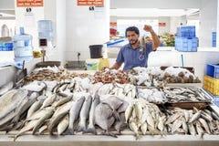 Mannen säljer skaldjur på den lokala fiskmarknaden Fotografering för Bildbyråer
