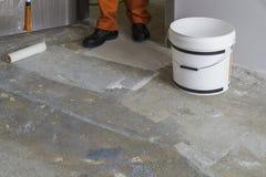 Mannen sätter abc-bok med rullen på konkret golv Hus under const Fotografering för Bildbyråer