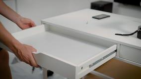 Mannen sätter in en vit skrivbordenhet in i ramen och att justera metallhandböckerna, montering av möblemang arkivfilmer