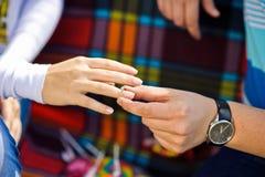 Mannen sätter kvinnan en förlovningsring på picknicken i bakgrunden Royaltyfria Foton