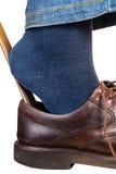 Mannen sätter på bruna skor genom att använda upp horn- slut för sko Arkivfoto